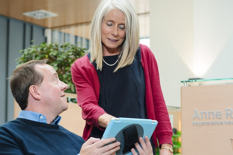 a woman standing behind a man, pointing out something to him on a tablet computer