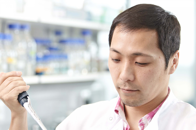 Researcher wearing a lab coat using a pipette