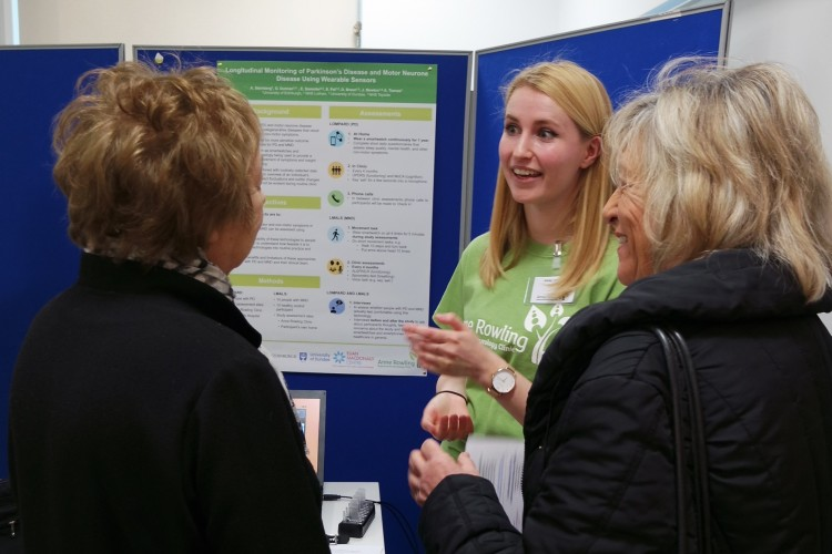 Researcher in Green T-Shirt talking to two ladies