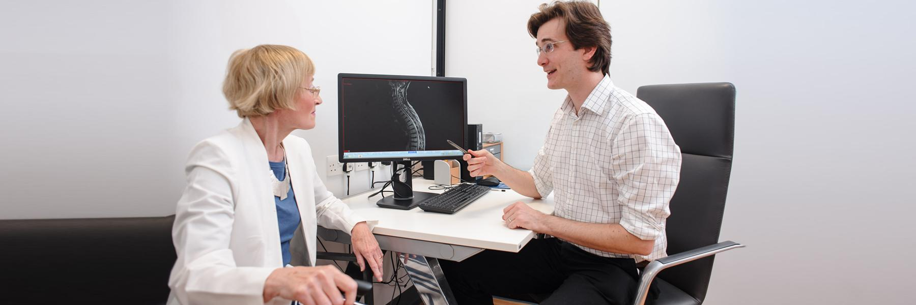 older female patient chatting to doctor in a clinic