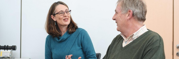 Woman smiling and chatting to man
