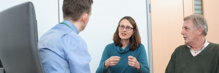 a woman and a man talking to a male doctor,