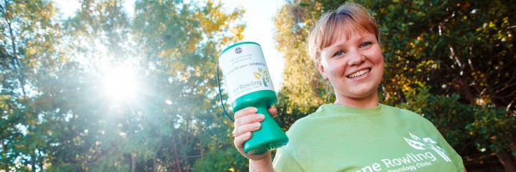 Young woman holding Anne Rowling Clinic collecting can smiling at camera
