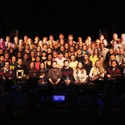 The cast of medics musical all sat on a stage